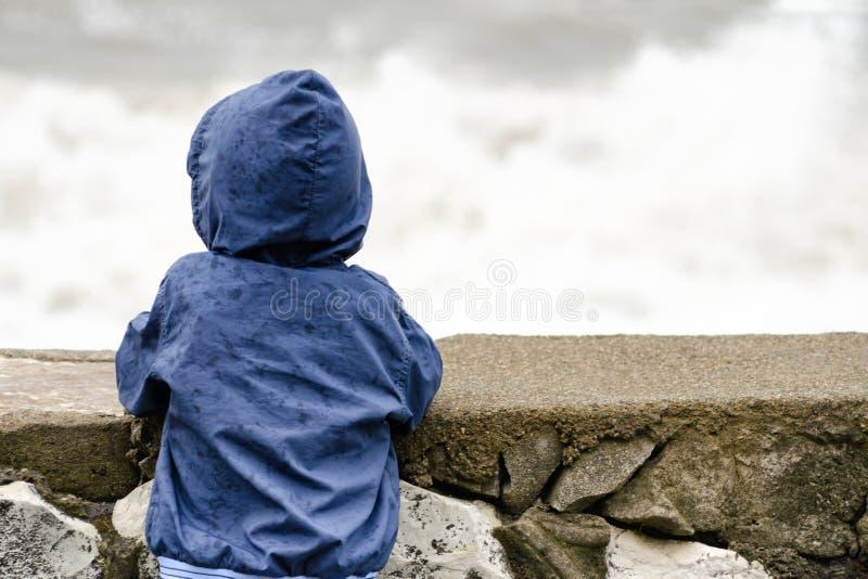 De jongen in matroos met kap bevindt zich met zijn rug tegen de pijler tegen de achtergrond van overzeese golven royalty-vrije stock fotografie