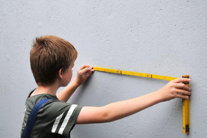 De jongen meet de muur met behulp van een vouwmeter stock afbeeldingen
