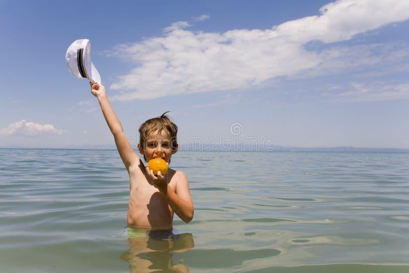 De jongen met een sinaasappel stock foto