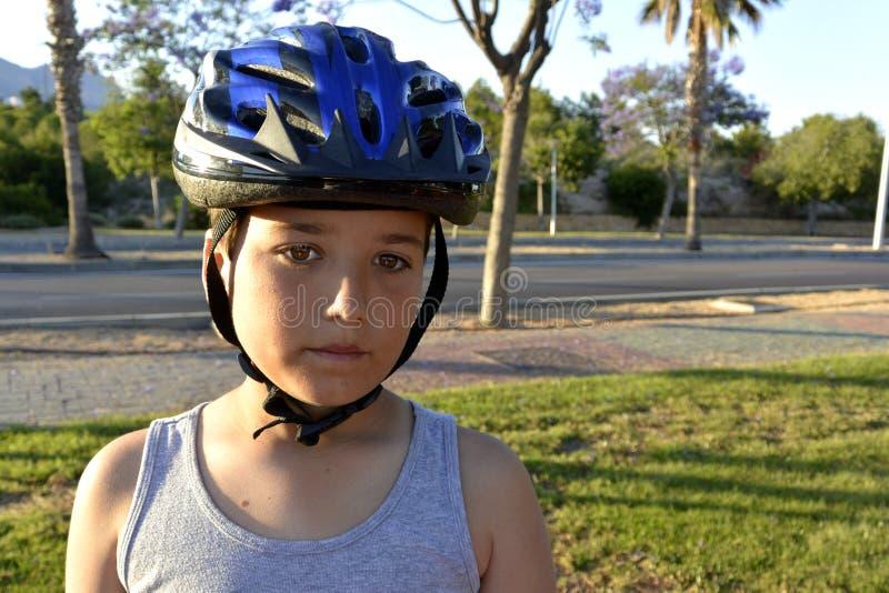 De jongen met helm berijdt MonoWheel op promenade stock foto