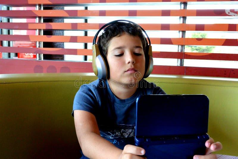 De jongen met hoofdtelefoons speelt met elektronisch Spel royalty-vrije stock afbeeldingen