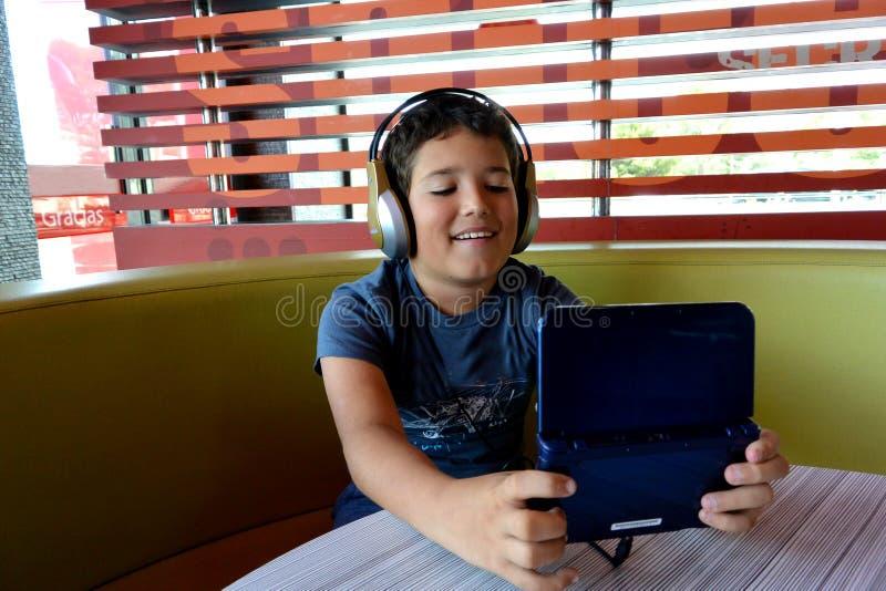 De jongen met hoofdtelefoons speelt met elektronisch Spel royalty-vrije stock foto's