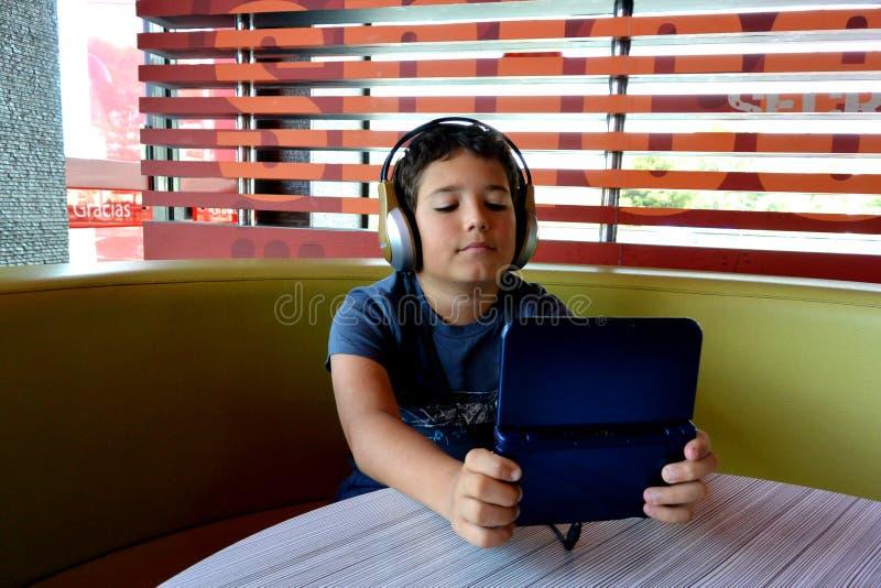De jongen met hoofdtelefoons speelt met elektronisch Spel royalty-vrije stock foto