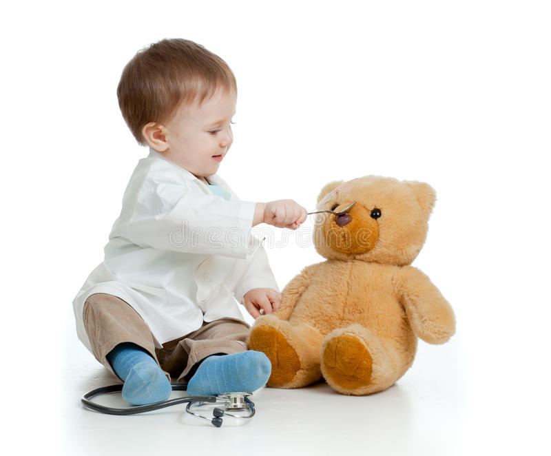 De jongen met kleren van arts voedt teddybeer stock foto