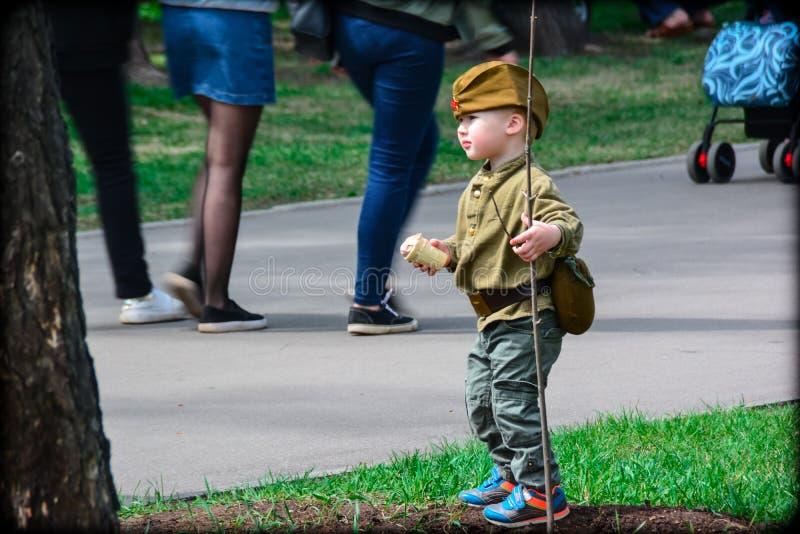 De jongen in militaire eenvormig met roomijs in hand in Victory Day kan 9, 2017, stock afbeelding