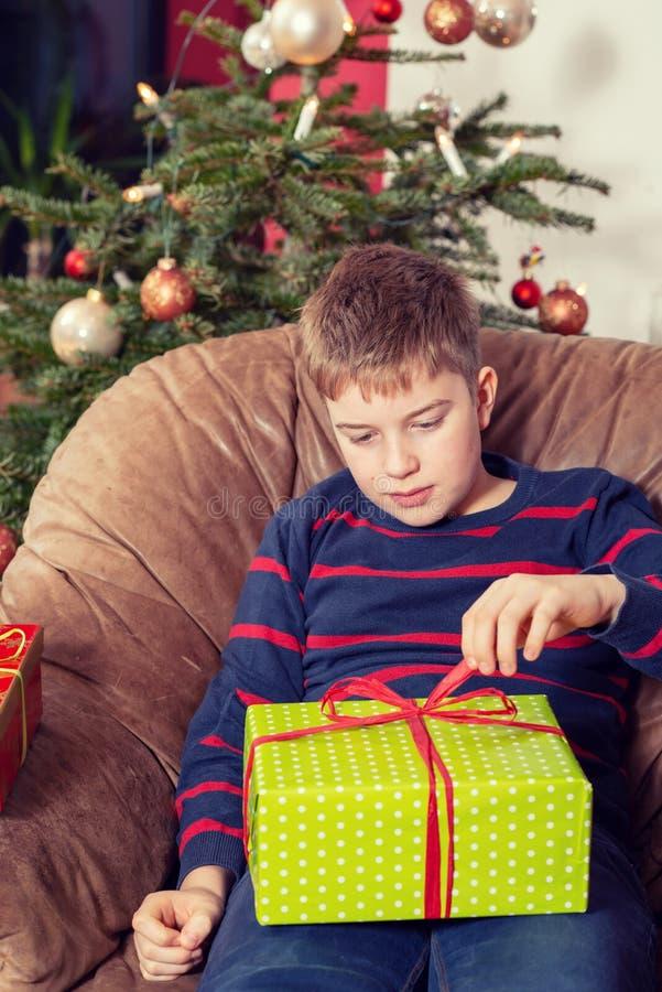 De jongen is niet zo gelukkig met zijn Kerstmis voorstelt royalty-vrije stock afbeelding