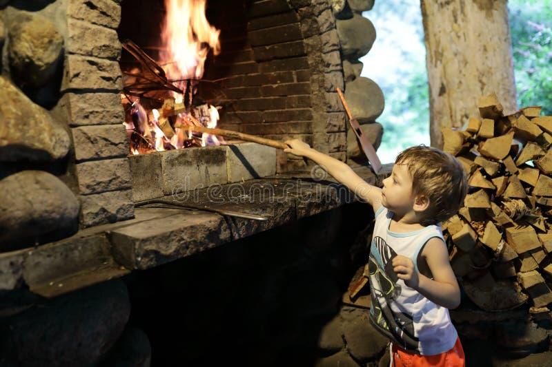 De jongen ontsteekt brand in open haard stock afbeelding