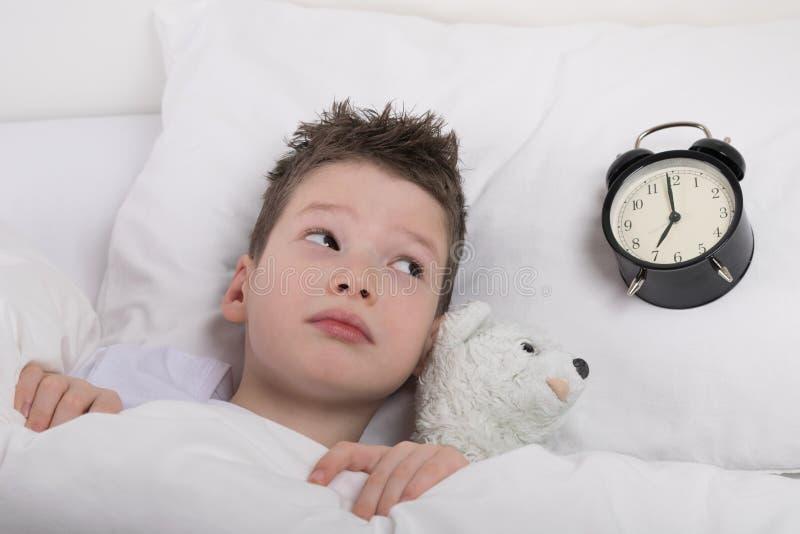 De jongen ontwaakt en bekijkt de wekker, hoeveel tijd wordt verlaten royalty-vrije stock foto