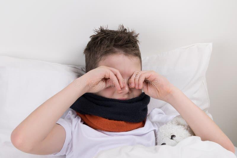 de jongen ontwaakte in bed, wil niet opstaan wrijft zijn ogen, kwetst zijn keel stock afbeeldingen