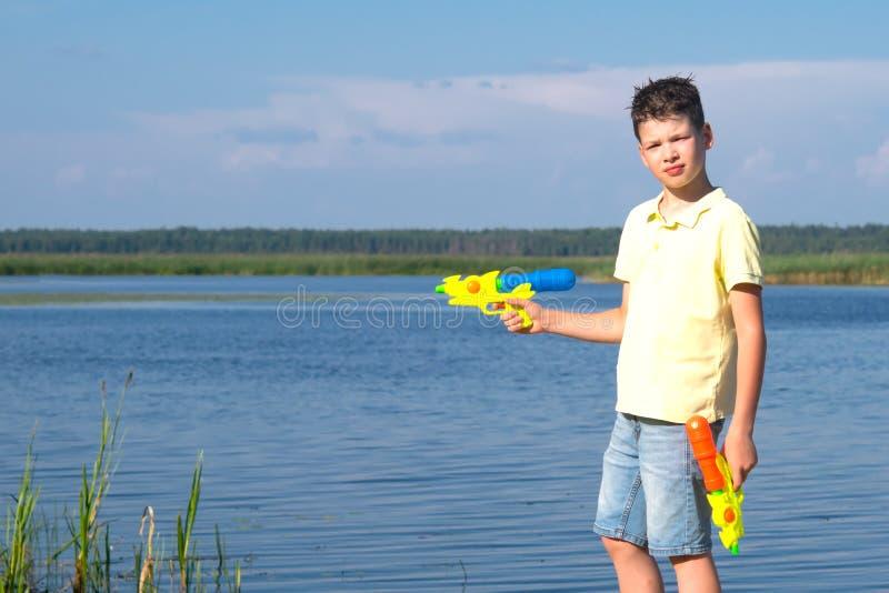 De jongen, op de achtergrond van een blauw meer en de hemel, het spelen waterpistolen royalty-vrije stock afbeeldingen
