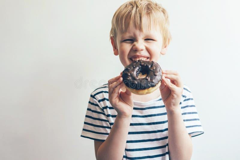 De jongen op een witte achtergrond houdt een chocoladedoughnut en lacht stock fotografie