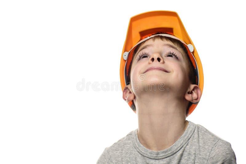 De jongen in de oranje bouwhelm hief omhoog zijn hoofd op Portret, gezicht Isoleer op witte achtergrond royalty-vrije stock afbeeldingen
