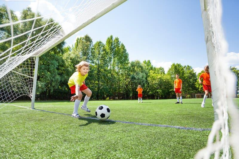De jongen probeert die voetbal te vangen bij houtbewerking wordt geworpen royalty-vrije stock foto