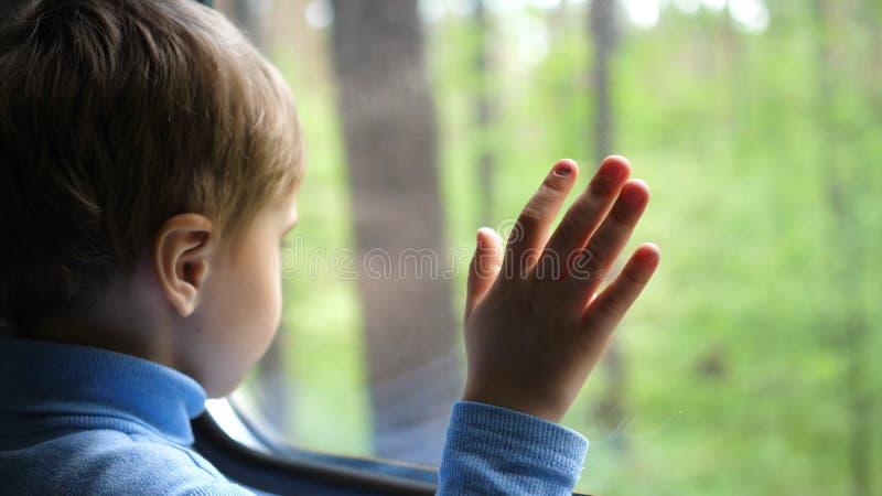 De jongen reist door trein en kijkt uit het venster, lettend op de bewegende voorwerpen buiten het venster Handclose-up royalty-vrije stock afbeeldingen