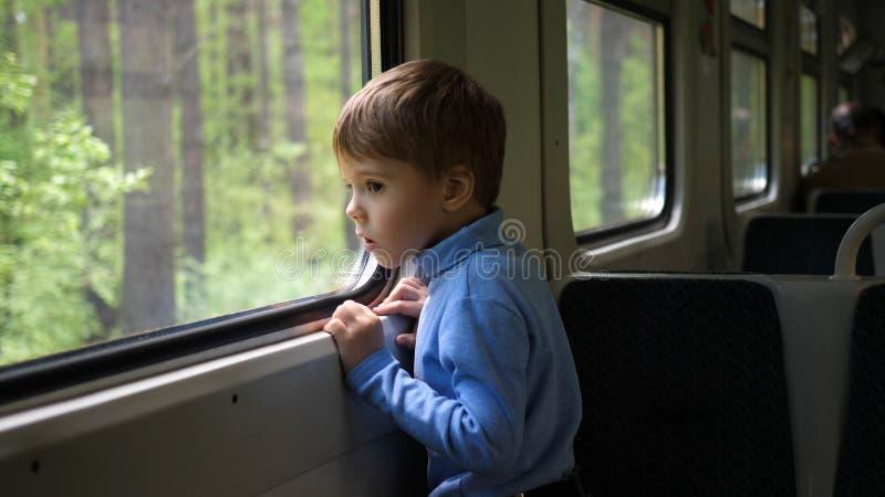 De jongen reist door trein en kijkt uit het venster, lettend op de bewegende voorwerpen buiten het venster Het reizen met stock fotografie