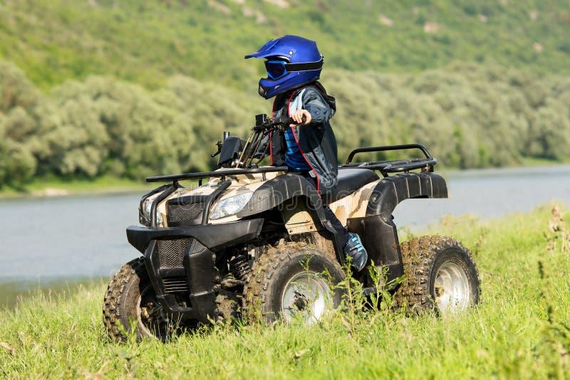 De jongen reist op een ATV stock foto