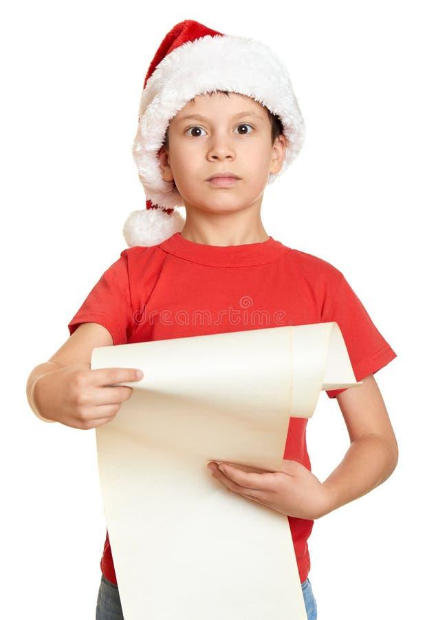 De jongen in rode hoed met lange rol wenst aan santa dit - Kerstmisconcept van de de wintervakantie stock foto's