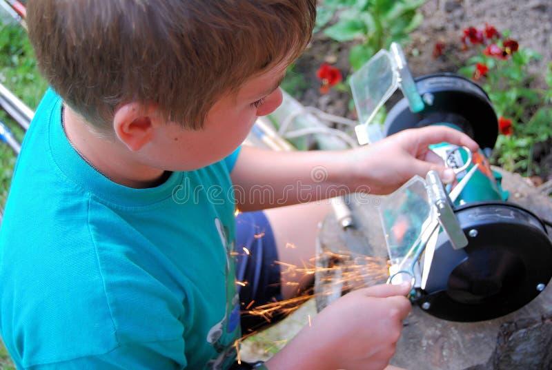 De jongen scherpt hulpmiddelen stock foto