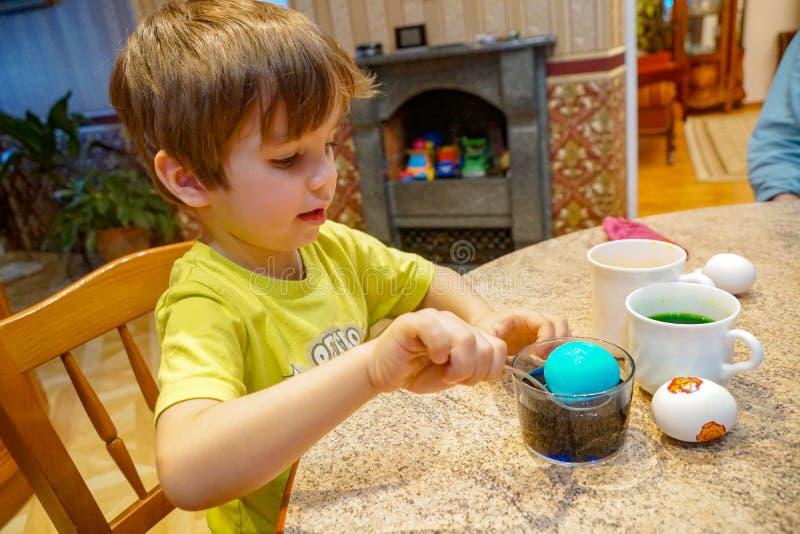 De jongen schildert eieren voor Pasen, de onderdompelingeneieren van de gebruikslepel in gekleurd water in het huisbinnenland stock afbeelding