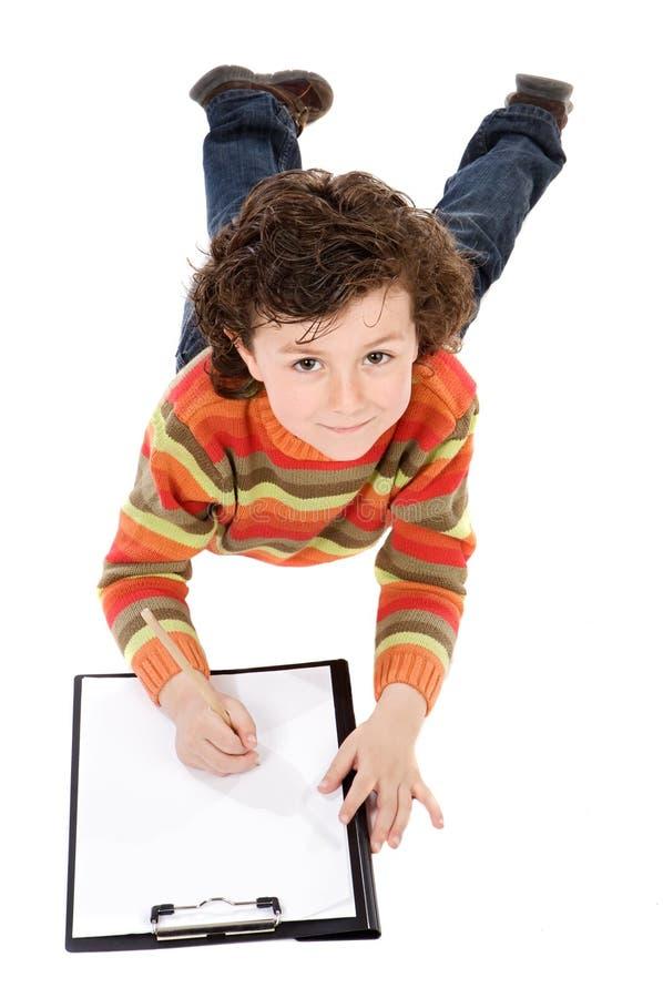 De jongen schrijft in klembord royalty-vrije stock foto's