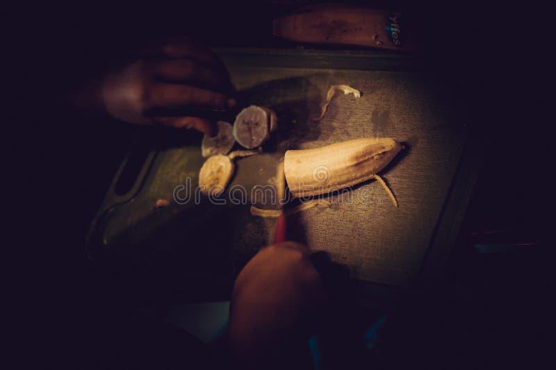 De jongen sneed bananen met een mes op de lijst, donkere onderbelichte scène stock afbeelding