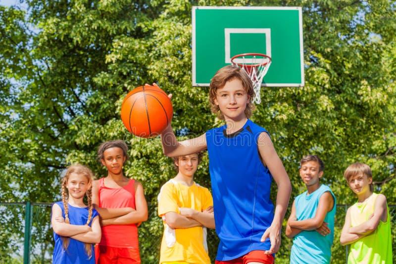 De jongen speelt basketbal met internationaal team royalty-vrije stock fotografie