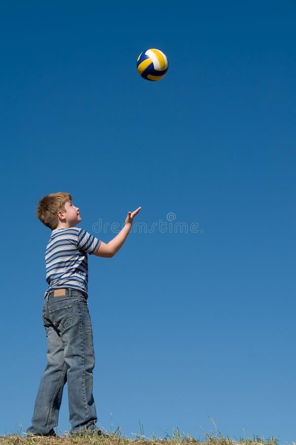 De jongen speelt een bal royalty-vrije stock afbeelding