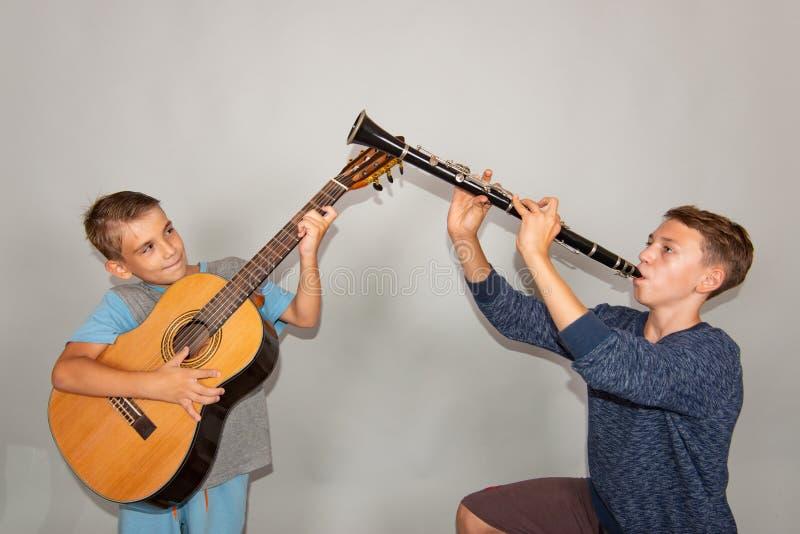 De jongen speelt de gitaar en de klarinet in verschillend stelt, stellend in de studio stock foto's