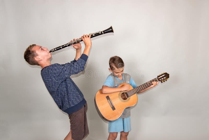 De jongen speelt de gitaar en de klarinet in verschillend stelt, stellend in de studio royalty-vrije stock afbeelding