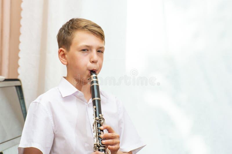 De jongen speelt de klarinet dichtbij de zwarte piano door het venster Musicologie, muziekonderwijs en onderwijs stock afbeelding