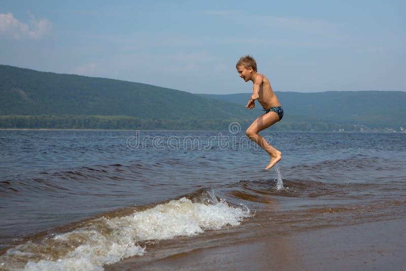 De jongen springt over de golven op het strand Zonnige de zomerdag stock afbeeldingen