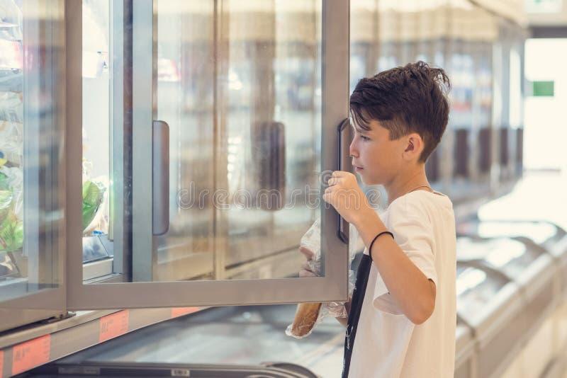 De jongen in de supermarkt die zich voor de diepvriezer dichtbij de glasdeuren bevinden royalty-vrije stock foto