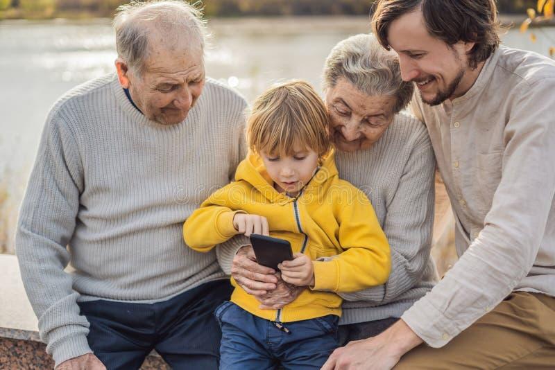 De jongen toont de foto op de telefoon aan zijn grootouders royalty-vrije stock afbeeldingen