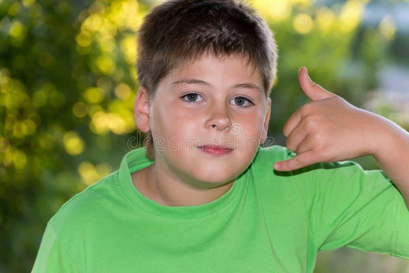 De jongen toont gebaar sprekend op telefoon stock foto