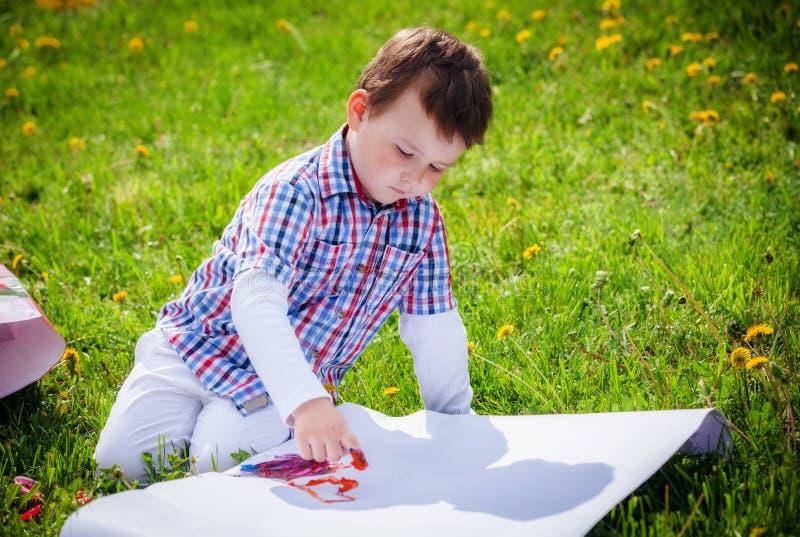 De jongen trekt op het gras royalty-vrije stock foto