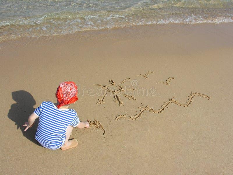 De jongen trekt op strand stock afbeeldingen