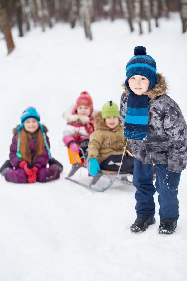De jongen trekt sleeën met jongere kinderen in de winterpark royalty-vrije stock afbeelding