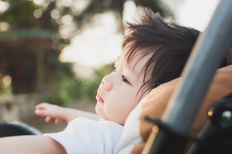 De Jongen van babyazië in Wandelwagen met ogen het staren stock fotografie