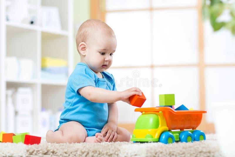 De jongen van de babypeuter het spelen met stuk speelgoed auto royalty-vrije stock foto