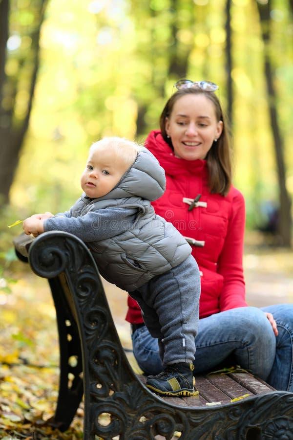 De jongen van de één éénjarigebaby in de herfstpark met zijn moeder stock afbeelding