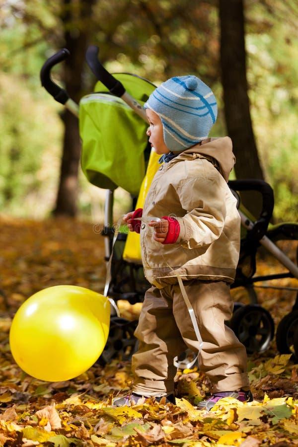De jongen van de baby in de herfstbladeren het houden royalty-vrije stock afbeeldingen