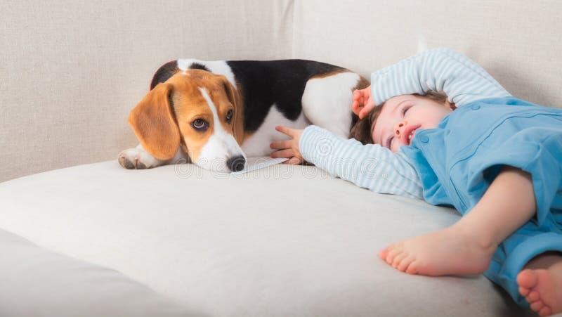 De jongen van de baby en zijn hond stock afbeeldingen