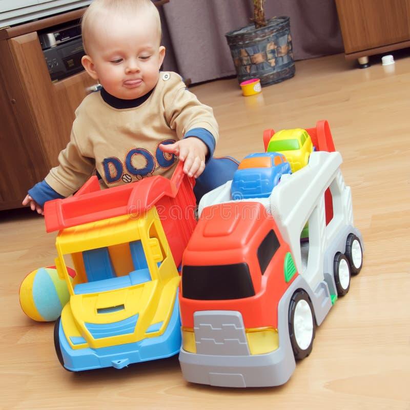 De jongen van de baby het spelen met vrachtwagens stock afbeeldingen