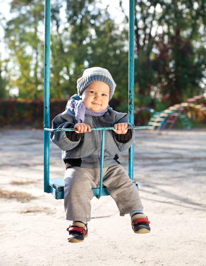 De jongen van de baby het spelen op schommeling in de herfstpark royalty-vrije stock foto