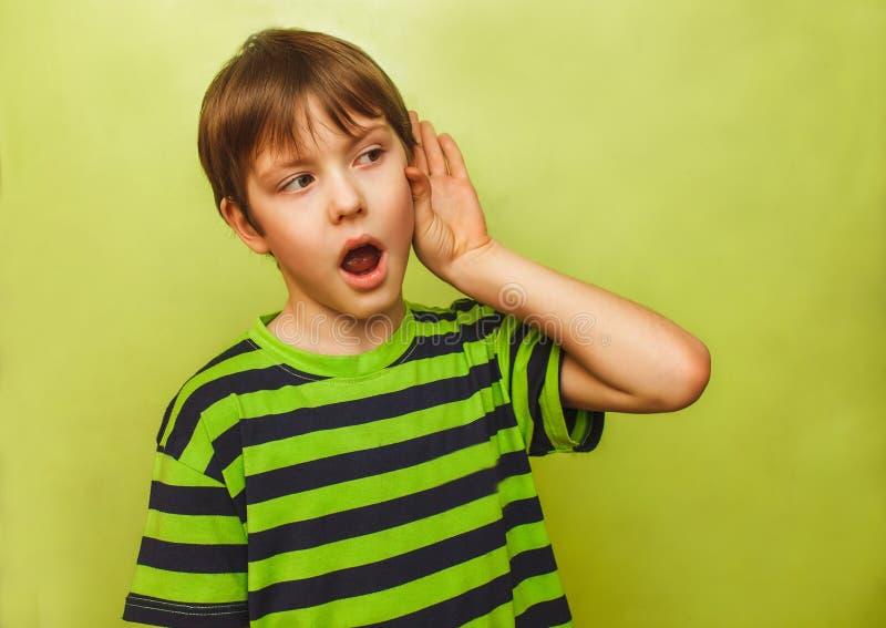 De jongen van de babytiener luistert om een hand aan te zetten zijn oor royalty-vrije stock afbeeldingen