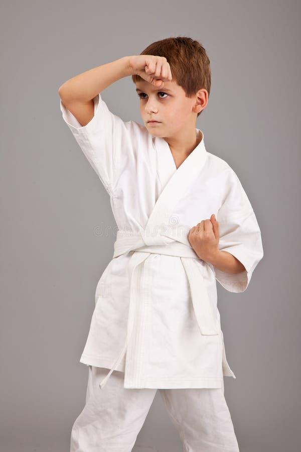 De jongen van de karate in het witte kimono vechten royalty-vrije stock foto