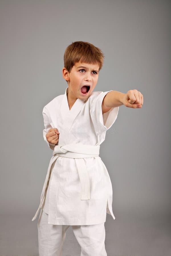 De jongen van de karate in het witte kimono vechten stock afbeelding