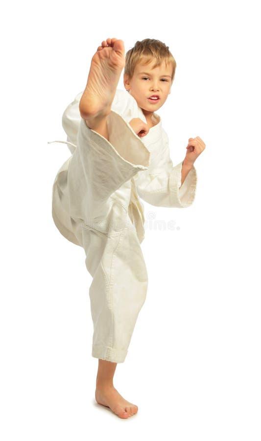 De jongen van de karate schopt een been