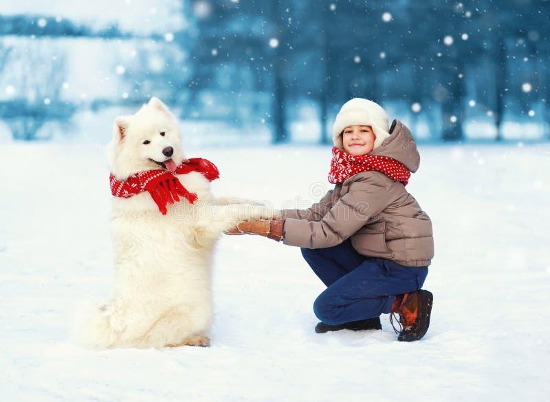De jongen van de Kerstmis het gelukkige tiener geeft spelen met witte Samoyed-hond op sneeuw in de winterdag, vrolijke hond pootk royalty-vrije stock fotografie