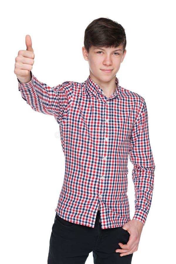 De jongen van de maniertiener houdt zijn duim tegen stock foto